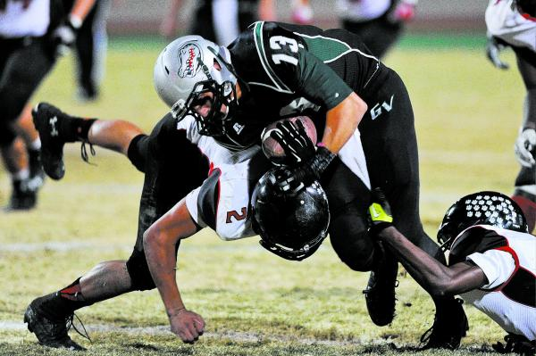 Green Valley's Kyler Chavez (13) is tackled by Las Vegas defender Jacob Littlefield (2) on Friday. Chavez had nine catches for 88 yards.
