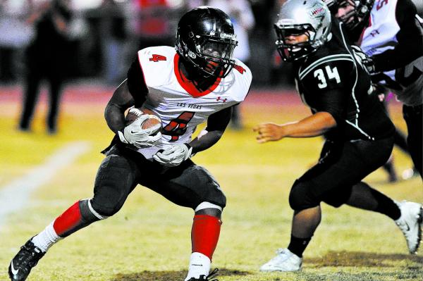 Las Vegas running back Elias Miller (4) looks for running room in front of Green Valley's Blaze Brooks (34) on Friday. Miller had a 10-yard TD run, but the Gators topped the Wildcats, 39-38.