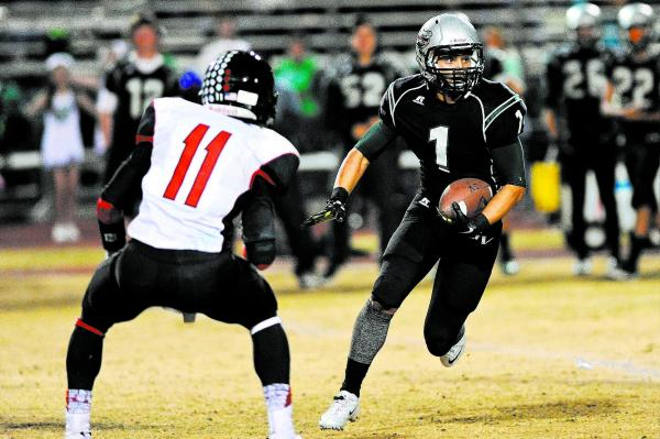 Green Valley's Giovanni Hernandez (1) looks for running room against Las Vegas defender Aaron Zanin-Banks (11) on Friday. Hernandez had five catches for 128 yards and two TDs in Green Valley's 39- ...