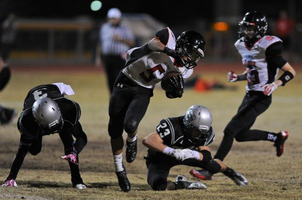 Las Vegas running back Andrew Moreland (5) tiptoes between Green Valley's Jacob Tomlin (3) and Albert Lake (23) on Friday. Moreland rushed for 174 yards and two TDs.