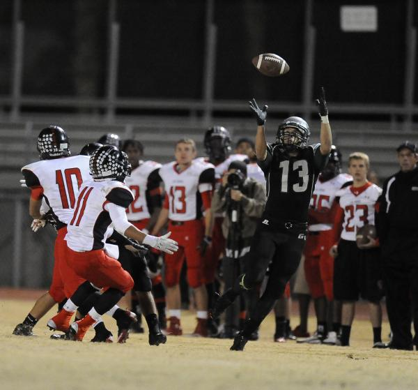 Green Valley's Kyler Chavez (13) leaps to catch a tipped pass as Las Vegas' Aaron Zanin-Banks (11) looks on.