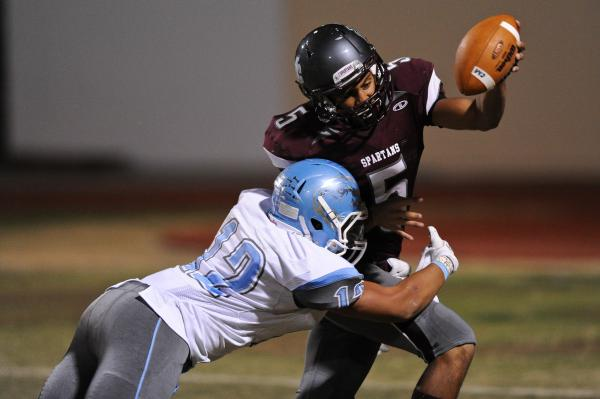 Cimarron's Derek Morefield (5) is wrapped up by Centennial's Izaias Jackson (12) on Thursday.