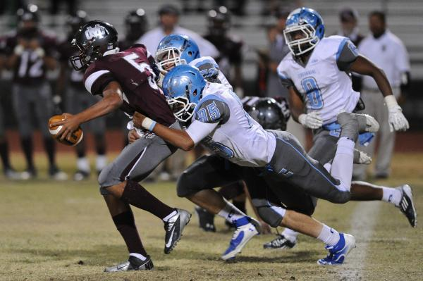 Cimarron's Derek Morefield (5) is brought down by a host of Centennial defenders including Andre Diller (85) on Thursday.