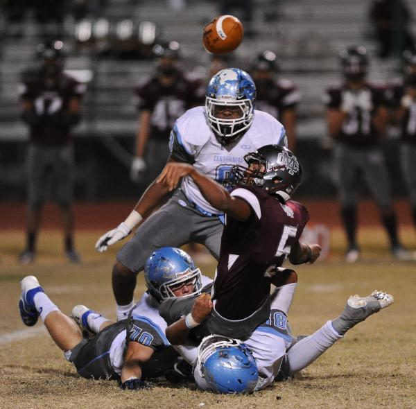 Cimarron's Derek Morefield (5) loses the ball after being tackled by Centennial defenders on Thursday.