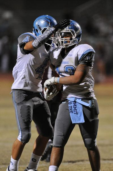 Centennial's Izaias Jackson (12) is congratulated by Nicholas Humenik after an interception during the team's 20-0 win over Cimarron-Memorial.