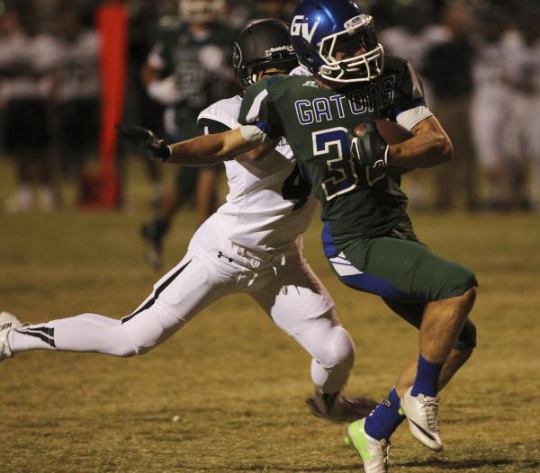Green Valley's Conor Perkins (33) gets taken down by Palo Verde's Darrion Finn (4) on Friday. Perkins had four catches for 35 yards and hit the game-winning extra point in overtime in a 42-4 ...