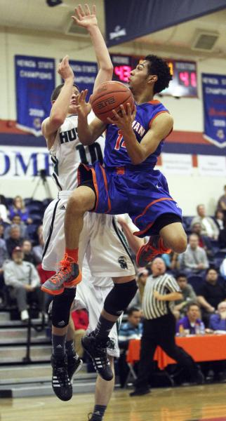 Gorman's Noah Robotham (14) goes up for a basket while being guarded by Sheldon's Matt Manning (10) on Thursday. Robotham had 12 points, six rebounds and seven assists in Gorman's 65-49 win.