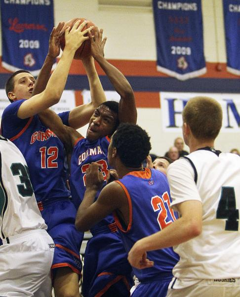 Gorman's Zach Collins (12) and Nick Blair (23) both grab a rebound as teammate Deon Whiteside (21) and Sheldon's and Ian Miller (4) look on Thursday.