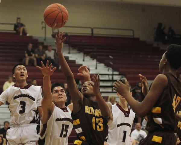 Bonanza's Jamal Logan (13) shoots while surrounded by Desert Oasis' Austin Vasquez (15), Jay Esguerra (3) and Kodi Leslie (1) on Friday.