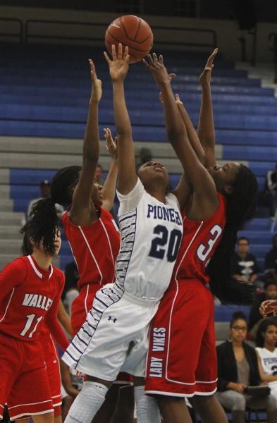 Canyon Springs' Alexia Thrower (20) has her shot contested by Valley's Eimainei Thomas-Palmer, right, and Alaihya Williams (3) on Tuesday. Thrower and the Pioneers rallied for a 62-59 home win.