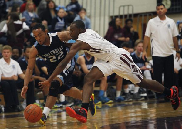 Centennial's Aaron Turner (22) and Cimarron-Memorial's Tony Harrison (11) battle for a loose ball on Friday.