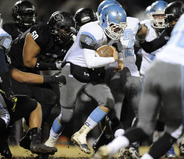 Centennial's Coll Thomson (7) is grabbed from behind by Palo Verde's Michael Hughes (50)