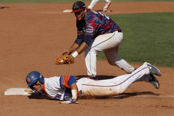 Bishop Gorman's Jerrel Latham slides safely back into third base under the tage of Julian Burrola of Coronado in the Division I baseball state final at College of Southern Nevada.
