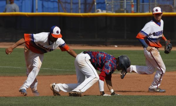 Bishop Gorman's Kai Domingo, left, tags out Coronado's Cain Brady during the first game on Saturday. The Cougars won that contest 11-7, then beat Gorman 7-4 in the second game to claim the Divisio ...