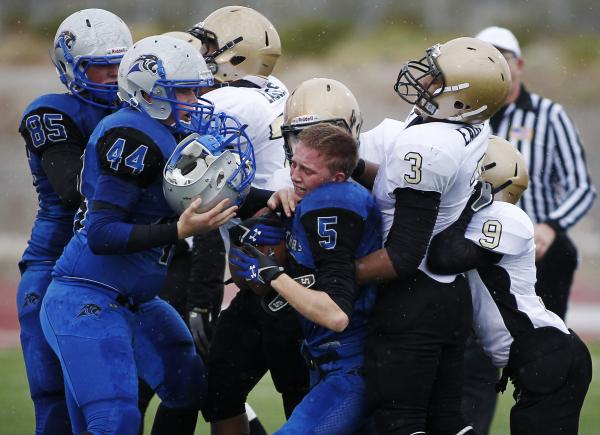Pahranagat Valley's Wade Leavitt (5) is wrapped up as his helmet flies off and is caught by teammate Paden Higbee.