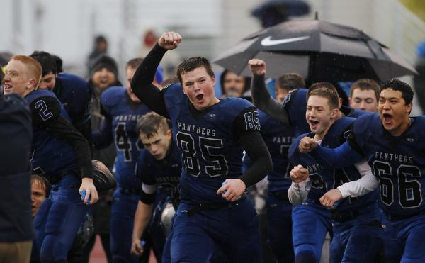 Pahranagat Valley's Jake Carter (85) leads his team in celebration as the Panthers win the Division IV state title.