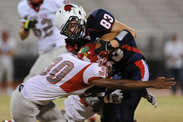Coronado receiver Brian Johnson (83) is wrapped up by Arbor View defender C.J. Smith (30) on Friday.