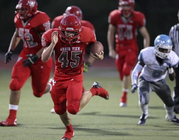 Arbor View running back Ricky Clark goes for 73 yards on the first play from scrimmage against Centennial on Thursday night. Clark was dragged down at the 7, but the run set up the Aggies' first s ...