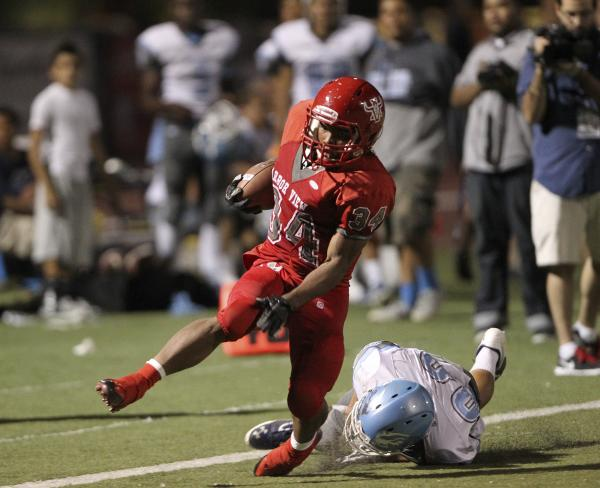Arbor View running back Herman Gray is tripped up by Centennial defensive back Samuel Liaga during a 47-yard run in the second quarter on Thursday. Gray ran for 117 yards and a touchdown in a 35-8 ...