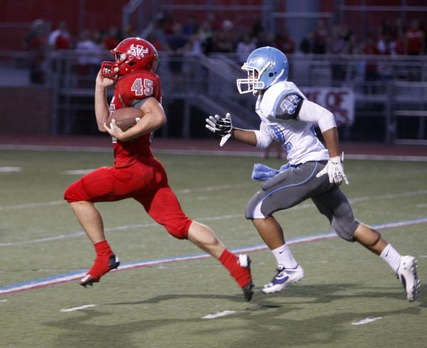 Arbor View running back Ricky Clark runs ahead of Centennial defensive back Samuel Liaga for 73-yard gain on the first play from scrimmage on Thursday. The run set up a touchdown, and the Aggies n ...