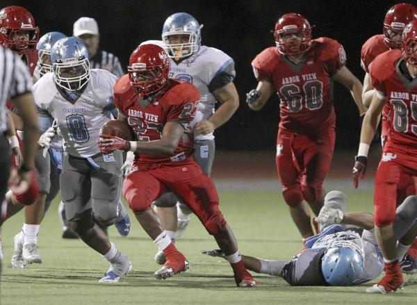 Arbor View fullback Denajiou McZeal runs ahead of Centennial defender Haikeem Arnold in the fourth quarter. McZeal and the Aggies gained 300 yards, all on the ground, in a 35-8 home win.