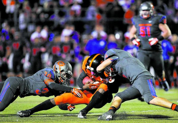 Bishop Gorman's Dylan Weldon (30) and Nico Fertitta (4) converge on Booker T. Washington quarterback Treon Harris (5) on Friday. Harris rushed for one TD and passed for three more in a 28-12 win.