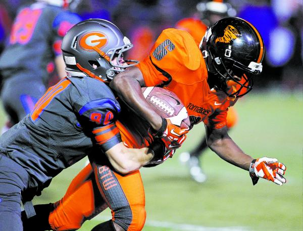 Bishop Gorman's Karl Regan (80) tackles Booker T. Washington's Shaquille Green (6) from behind on Friday.