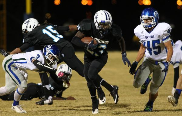Canyon Springs' Zaviontay Stevenson looks for running room as Green Valley's Anthony Finni (45) closes in.