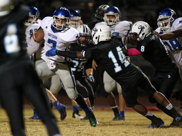 Green Valley's Christian Lopez tries to elude Canyon Springs' Jaquan Ashley (14) on Thursday.