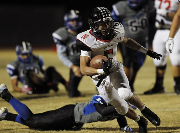 Las Vegas' Andrew Moreland (5) gets past Basic's Brian Evans (7) on Friday night. Moreland rushed for 114 yards and one touchdown and caught a TD pass in a 63-24 win.