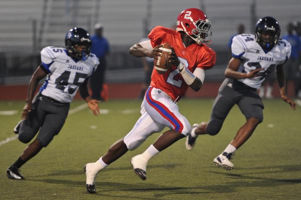 Valley quarterback Tyrone Prewitt (2) scrambles away from Desert Pines defenders Tevin Moore (45) and Milton Wallace (34) on Thursday night.