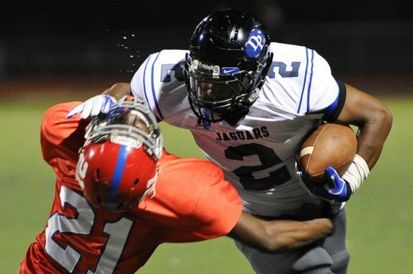 Desert Pines running back Eric Wilkes (2) stiff arms Valley defender Malik Batiste (21) on Thursday. Wilkes ran for 92 yards on 13 carries in a 45-14 win.