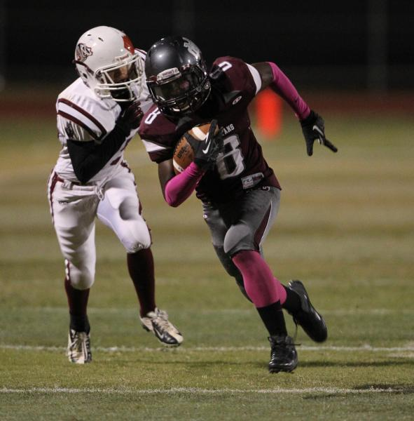 Cimarron-Memorial wide receiver Maurice Bennett runs ahead of Desert Oasis defensive back Hunter Amos for a 48-yard touchdown in the first quarter on Friday.