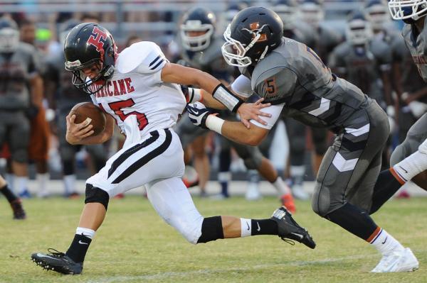 Legacy linebacker Mason Davis drags down Hurricane quarterback Adlai Elison (15) on Saturday.
