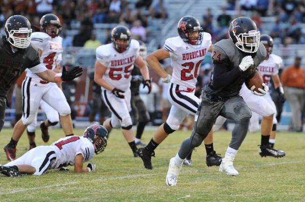 Legacy running back Casey Hughes (24) breaks free from Hurricane defensive back Jay Williams (21) and runs for a second-quarter touchdown on Saturday.