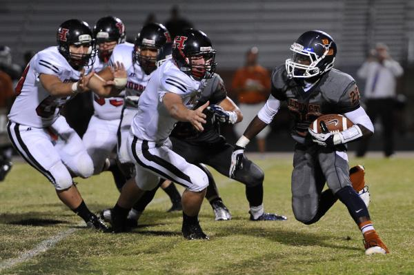 Legacy running back DeMichael Walker (22) runs past a host of Hurricane defenders on Saturday. Walker rushed for 178 yards and a touchdown and had a 99-yard kickoff return for another score in a 3 ...