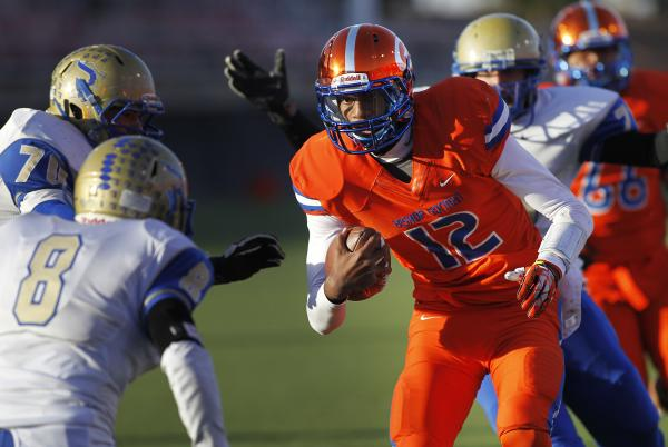 Bishop Gorman quarterback Randall Cunningham (12) looks for running room between Reed's Austin Warner (8) and Calvin Cox (70) on Saturday. Cunningham rushed for 213 yards and four TDs in a 48-13 w ...