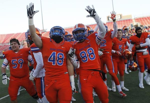 Bishop Gorman's Chris Lalli (48) and James Huber (88) celebrate their school's fifth consecutive state title.