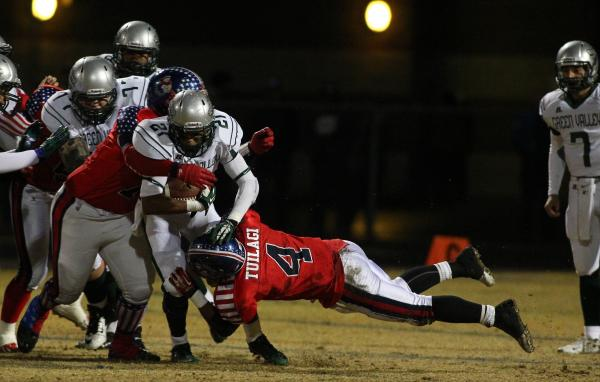Green Valley's Larry Norman tries to break a tackle by Liberty's Ethan Tuilagi (4).