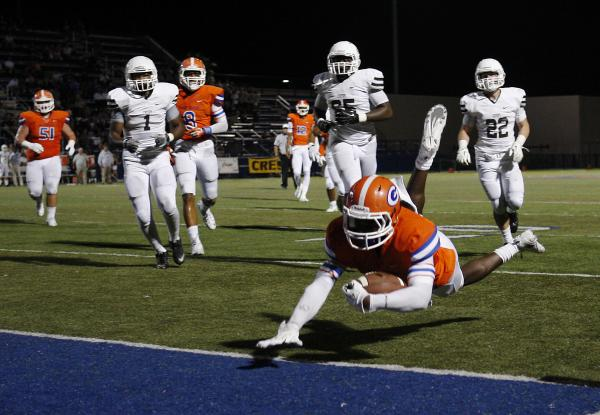 Bishop Gorman's Daniel Stewart dives into the end zone to score against Crespi (Calif.) on Friday. Stewart rushed for 117 yards and three TDs in a 42-9 win.