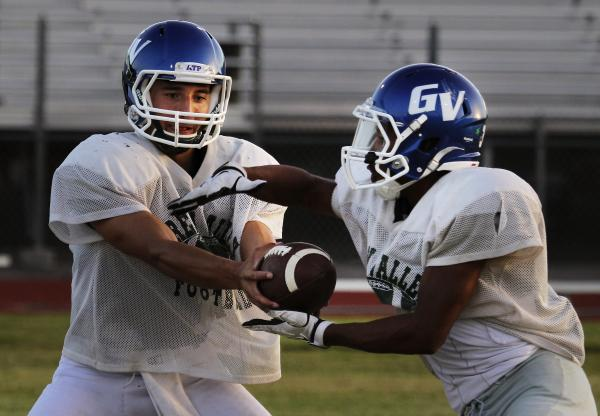 Green Valley quarterback Christian Lopez hands the ball off during practice. Lopez and the Gators are averaging 493.7 yards off offense, but are off to a 1-2 start.