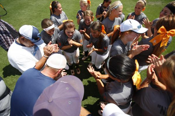 Centennial's softball team and coaches huddle and begin to celebrate their state championship.