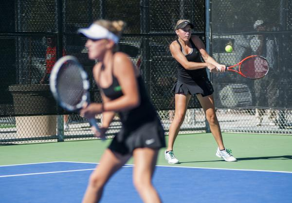 Palo Verde's Chloe Henderson, right, hits a backhand as Sophie Henderson waits near the net.