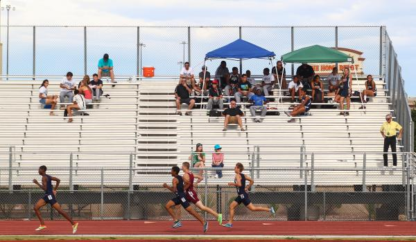 Spectators watch the Sunset Region boys 1,600-meter run, led by three Centennial runners. The Bulldogs finished 1-2-3 in the event and rolled to the team title.