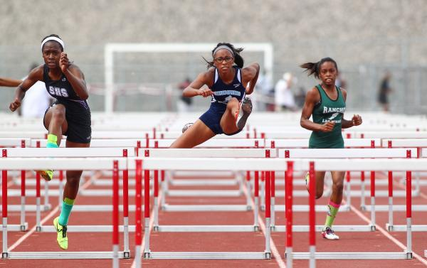 Canyon Springs' Courtney Robinson take the lead in the Sunrise Region girls 100-meter hurdles on Friday at Silverado. Robinson won the event, and also took the 300 hurdles and 100-meter dash.