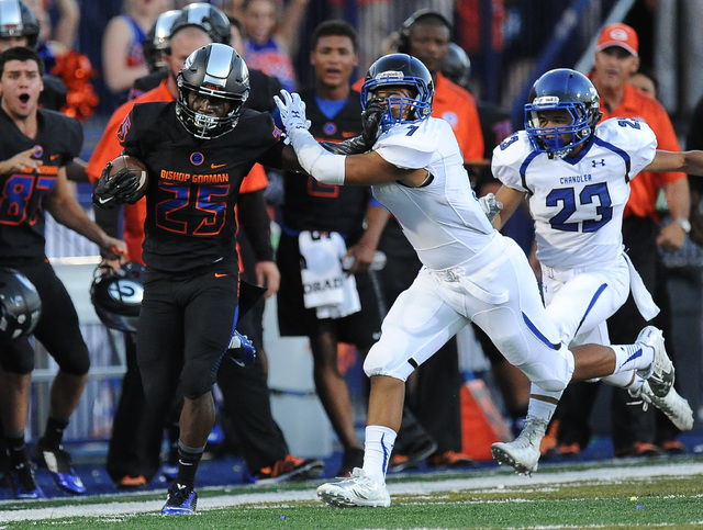 Bishop Gorman wide receiver Tyjon Lindsey (25) stiff-arms Chandler safety Teauntae Nash (7) in the first quarter of their high school football game at Bishop Gorman High School in Las Vegas Saturd ...