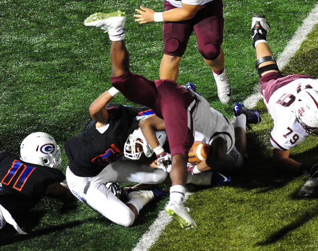 Don Bosco Prep Ironmen running back Malik Bakker is upended by Bishop Gorman linebacker Palaie Gaoteote (10) while rushing the ball in the second half of their prep football game at Bishop Gorman  ...