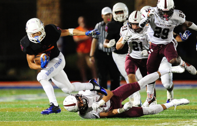 Bishop Gorman running back Biaggio Ali Walsh (7) breaks the tackle of Don Bosco Prep Ironmen safety Julian Conover to gain a first down in the second half of their prep football game at Bishop Gor ...