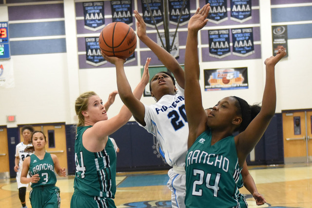 Canyon Springs Alexa Thrower (20) goes up for a shot against Rancho defenders Samantha Pochop (44) and Kyndal Ricks (24) during the Sunrise Regional quarterfinal basketball game played at the Cany ...