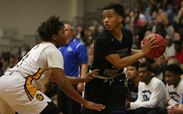 Desert Pines guard Capri Uzan (1) looks for an open teammate while being guarded by Clark's Keyshaun Webb (1) in the Division I-A Southern Region boys basketball final at Desert Pines High School  ...